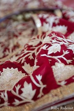 Pattern details on a red bridal lengha.