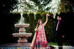 An Indian bride and groom celebrate at their pink themed reception.