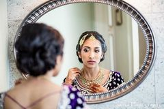This beautiful Indian bride gets ready for her big wedding with some fabulous hair and makeup. Her multi-hued lengha choli is gorgeous!