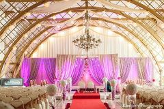 A mandap in a grand ballroom with pink lighting, white drapes, and gold accents.