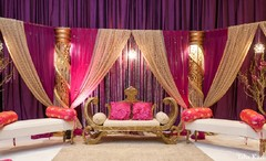 An Indian bride and groom celebrate at their wedding reception. They choose a bold pink palette.