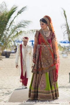 An Indian bride and groom take portraits on the beach.