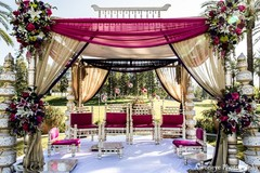 A pink and purple mandap for an outdoor wedding.
