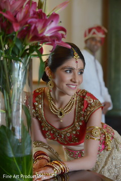 This Indian bride is beautiful in a red lengha with gold jewelry.