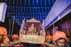 This Indian bride is carried in on a beautiful palanquin at her wedding ceremony.