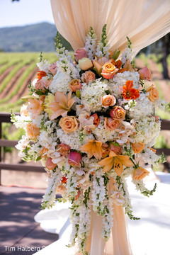 This outdoor Indian wedding ceremony features beautiful floral and decor.