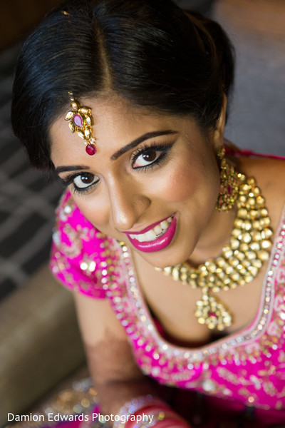 indian bride getting ready,indian bridal hair and makeup,tikka,gold indian wedding jewelry