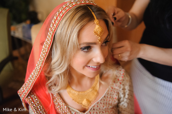 indian bride getting ready,tikka,indian bridal hair and makeup,gold indian wedding jewelry,indian wedding necklace