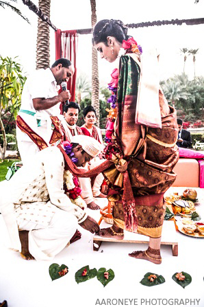 The groom places a ring on the foot of the bride.
