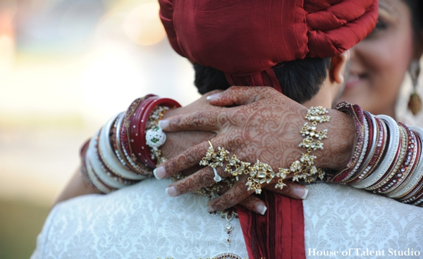 A portrait of the Indian bride and groom. in traditional ceremony dress. She wears traditional wedding jewelry.