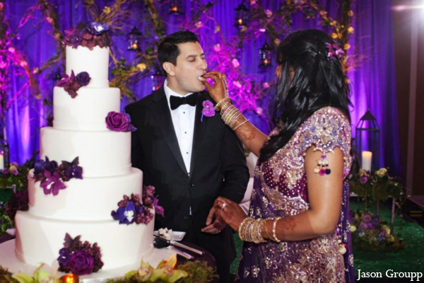 The Indian wedding reception. The bride and groom cut their wedding cake.
