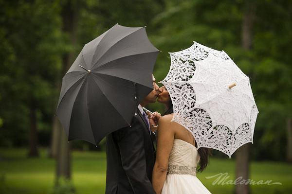 Indianbrideandgroomoutsideweddingkissingumbrellas