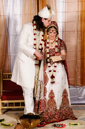 The bride and groom at their Indian wedding ceremony. They perform traditional wedding rituals and customs.
