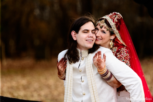 A portrait of the bride and groom on their wedding day. They are wearing traditional ceremonial dress. The bride in a lengha and the groom in a sherwani.