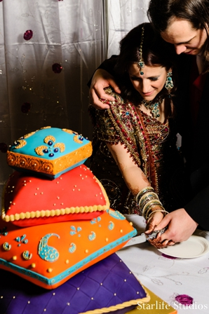 Featured Indian Weddings,orange,cakes and treats,indian wedding cake,reception wedding cake,colorful wedding cake,unique ideas for reception wedding cake,stacked pillows cake,bride and groom cutting cake,Starlife Studios