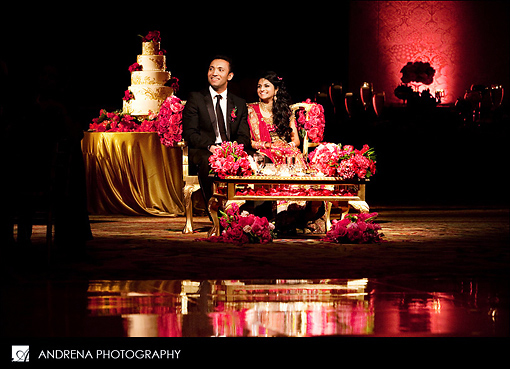 Indian bride and groom at sweetheart stage with cake behind