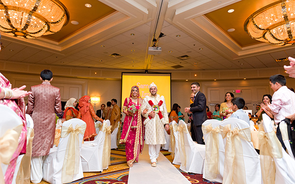 An Indian bride and groom walk into their Indian wedding reception.
