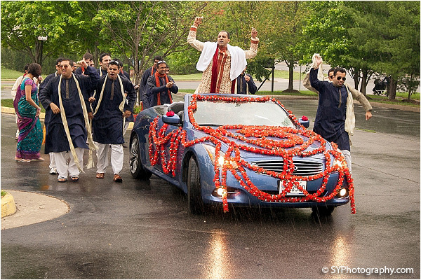 An Indian groom arrives to his Indian wedding in a baraat.