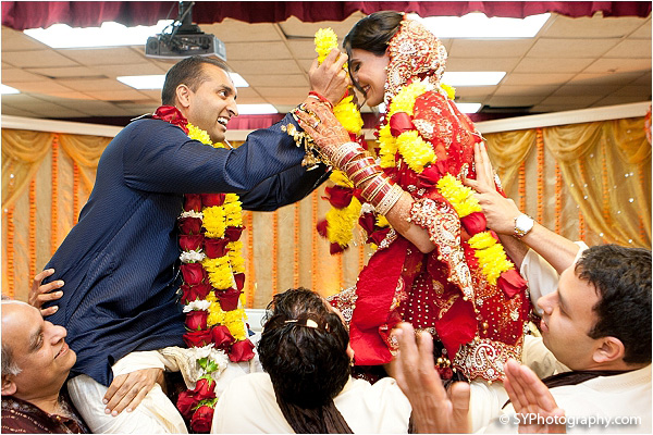 An Indian bride and groom give each other jaimalas, or flower wreaths.