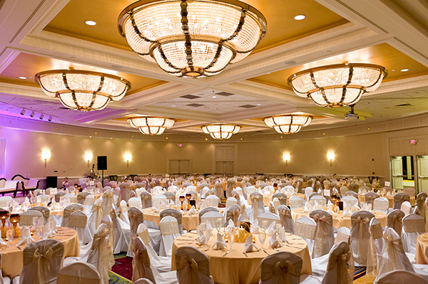 Indian wedding vendors decorate this ballroom in a modern style.