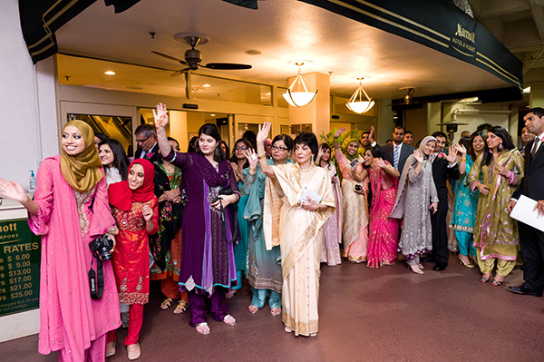 Friends and family wave goodbye to an Indian bride and groom as they depart.