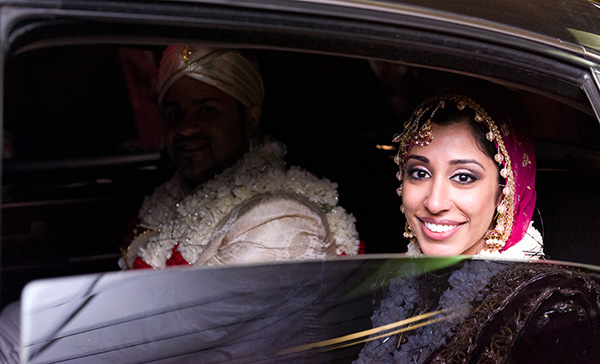 An Indian bride and groom depart their Indian wedding venue.