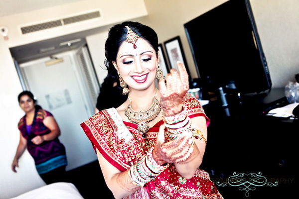 An Indian bride slips on churis, traditional Indian bracelet jewelry.
