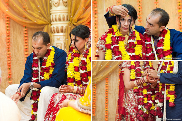 An Indian bride and groom wear red and yellow flower wreaths at their Indian wedding ceremony.
