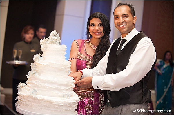 An Indian bride and groom cut into their grand Indian wedding cake.