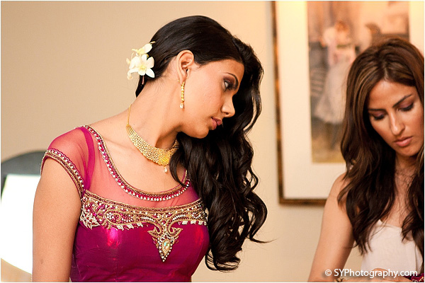 An Indian bride wears a hot pink bridal lengha as she prepares for her Indian wedding reception.