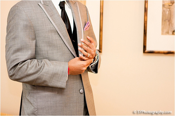 A groom wears a modern grey suit to his Indian wedding reception.
