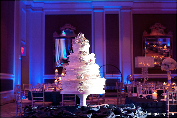A four tiered Indian wedding cake stands tall at this elegant Indian wedding reception.