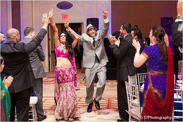An Indian bride and groom make a grand entrance into their Indian wedding reception.