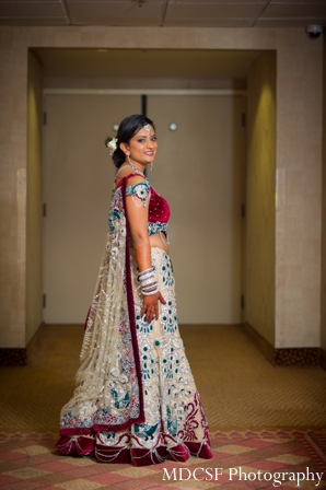 Indian bride in indian bridal jewelry matching her wedding lengha.
