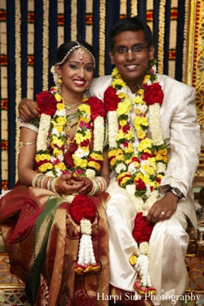 Indian bride and groom wear their jaimala flower garlands.