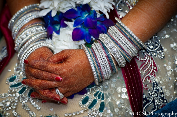 Indian bridal jewery shown on arms decorated with bridal henna.