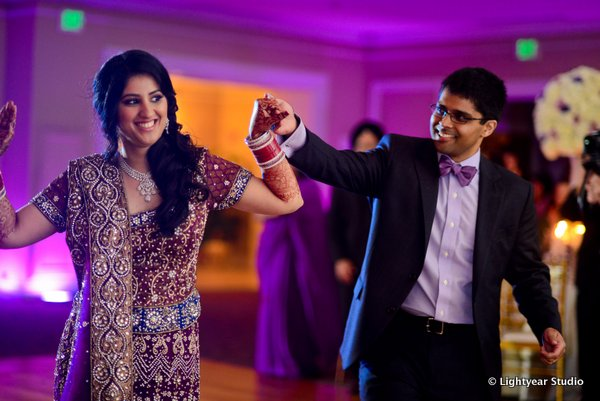 An Indian bride wears a purple bridal lengha at her Indian wedding reception.