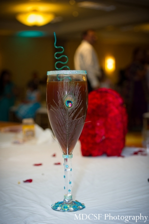 Peacock theme indian wedding party shown on champagne glass.