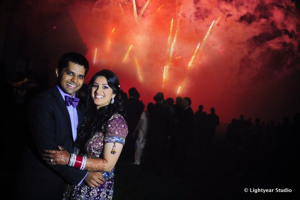 An Indian bride and groom with a fireworks show to end their Indian wedding.