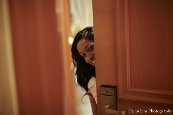 An Indian bride peeks out as she gets ready for her indian wedding.