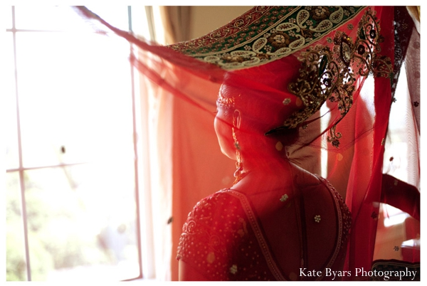 A red chuni is placed on this indian bride's head.