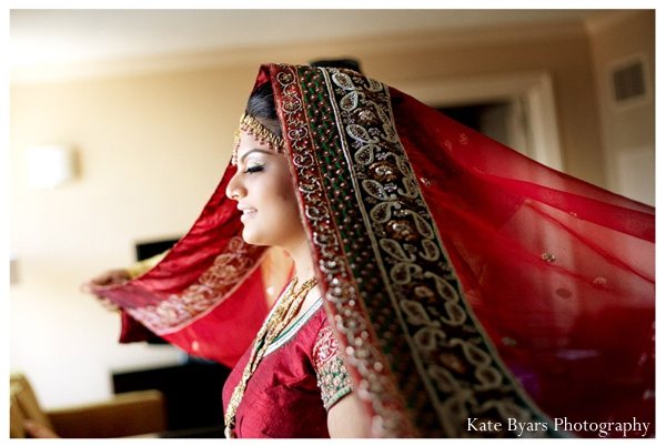 Indian bride dresses in a traditional red lengha for her Indian wedding.