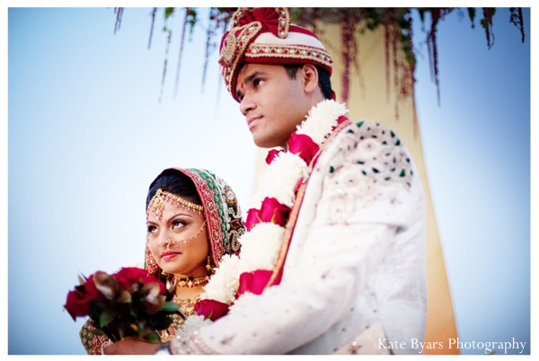 An Indian bride and her groom in traditional indian wedding outfits.