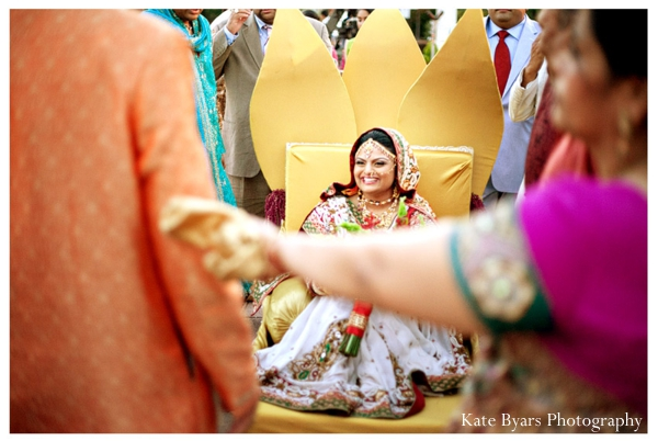 An Indian bride arrives on a yellow palanquin to her indian wedding.