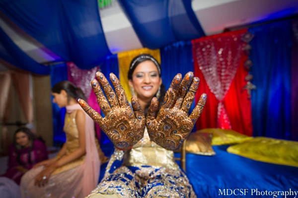 Bridal mehndi on hands with touches of blue.
