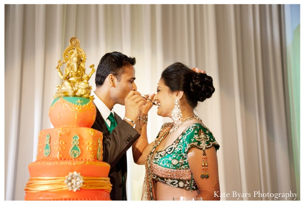 Indian bride and groom feed each other pieces of indian wedding cake.