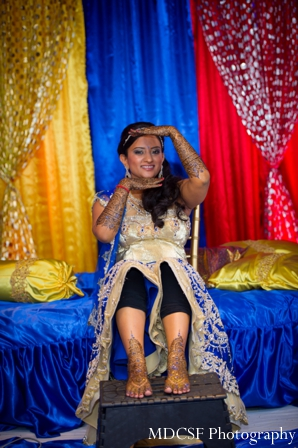 Indian bride shows off her bridal mehndi on her arms and feet.
