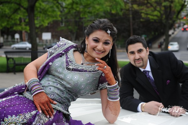 An Indian bride poses with her groom for an Indian wedding photographer.