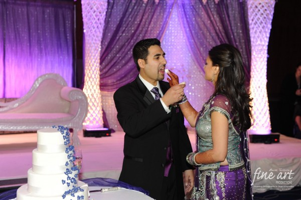 An indian bride and groom feed eachother their Indian wedding cake.