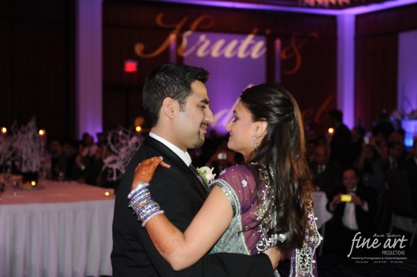 An Indian bride and groom dance at their modern purple indian wedding reception.